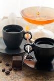 Dos tazas de café y granos de café asperjados con el postre Fotos de archivo libres de regalías