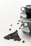 Dos tazas de café y granos de café derramados Foto de archivo libre de regalías
