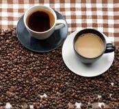 Dos tazas de café y granos de café en un paño a cuadros Fotografía de archivo libre de regalías