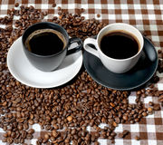 Dos tazas de café y granos de café en un paño a cuadros Imagen de archivo