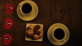Dos tazas de café y de velas en la tabla en un café metrajes