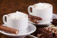 Dos tazas de café o de cacao caliente con los chocolates y las galletas encendido Foto de archivo