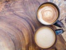 Dos tazas de capuchino caliente del café en el fondo de madera de la textura, a Fotos de archivo
