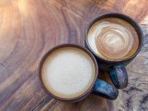 Dos tazas de capuchino caliente del café en el fondo de madera de la textura adentro Imágenes de archivo libres de regalías