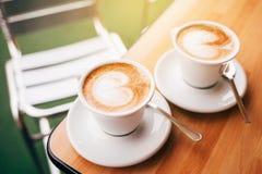 Dos tazas de capuchino con arte del latte Imagen de archivo libre de regalías
