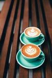 Dos tazas de capuchino con arte del latte Imágenes de archivo libres de regalías