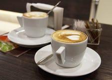 Dos tazas de capuchino en estilo romántico sirvieron en café Fotos de archivo
