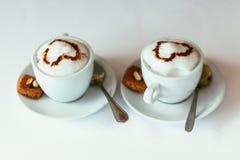Dos tazas de capuchino gastrónomo del café con las galletas contra Imagen de archivo