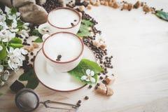 Dos tazas de capuchino recientemente elaborado cerveza, espumoso Granos de café, chocolate y azúcar de caña derramados Fotos de archivo