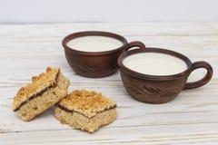 Dos tazas de cerámica viejas de leche y de dos pedazos de empanada rallada Fotografía de archivo