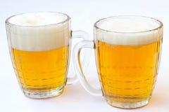 Dos tazas de cerveza en el fondo blanco Imagen de archivo libre de regalías
