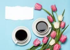 Dos tazas de coffe y tulipanes rosados en fondo azul Imagen de archivo libre de regalías
