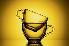 Dos tazas de cristal transparentes para el té Fondo amarillo, primer, DISPOSICIÓN HORIZONTAL fotografía de archivo libre de regalías