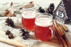 Dos tazas de invierno hacen la cerveza a mano con el casquillo de la espuma Imágenes de archivo libres de regalías
