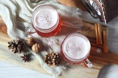 Dos tazas de invierno hacen la cerveza a mano en decoraciones del Año Nuevo Fotografía de archivo libre de regalías