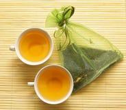 Dos tazas de la porcelana y un bolso de seda con té Imagen de archivo libre de regalías