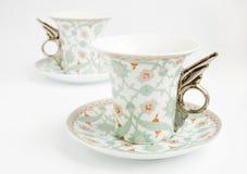 Dos tazas de la vendimia con las manetas en la forma de alas Imagen de archivo libre de regalías