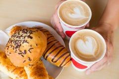 Dos tazas de latte con el corazón y las tortas Fotografía de archivo