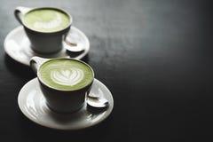 Dos tazas de latte del matcha en la tabla negra Imagen de archivo libre de regalías