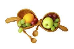 Dos tazas de madera con la fruta en un fondo blanco Foto de archivo