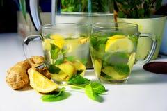 Dos tazas de té con la hierbabuena, el jengibre y el limón frescos Imagen de archivo