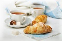 Dos tazas de té con los croissants en la mesa, una tonelada blanco-azul Foto de archivo