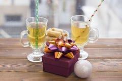 Dos tazas de té con paja, una caja de regalo, un cuenco de galletas y las bolas de un árbol de navidad Imagen de archivo libre de regalías