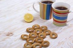 Dos tazas de té, de limón y de pequeños panecillos secos Imágenes de archivo libres de regalías