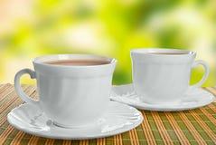 Dos tazas de té en fondo abstracto. Foto de archivo libre de regalías
