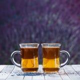 Dos tazas de té en un fondo de la lavanda colocan Espacio para el te Foto de archivo libre de regalías