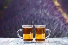 Dos tazas de té en un fondo de la lavanda colocan Espacio para el te Imágenes de archivo libres de regalías