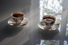 Dos tazas de té en una tabla de cristal Fotografía de archivo