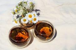 Dos tazas de té de manzanilla y de un ramo de manzanillas imagenes de archivo