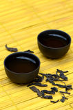 Tazas de té chinas y puerh salvaje en la estera amarilla Fotografía de archivo