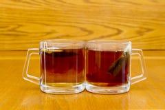 Dos tazas de té para el té de la mañana en la bolsita de té del balcón en fondo de madera Foto de archivo libre de regalías