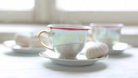 Dos tazas de té y de postre calientes en la tabla