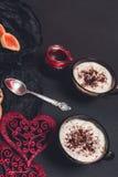 Dos tazas del café, capuchino cerca de corazones rojos en fondo negro de la tabla Día de tarjeta del día de San Valentín Amor Des Fotos de archivo