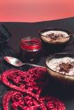 Dos tazas del café, capuchino cerca de corazones rojos en fondo negro de la tabla Día de tarjeta del día de San Valentín Amor Des Imagenes de archivo