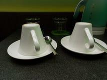 Dos tazas del café con leche y cucharas del té pusieron al revés con los vidrios y la caldera de agua en el fondo Imagen de archivo libre de regalías