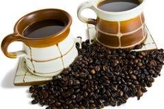 Dos tazas del coffe con los granos del coffe Foto de archivo libre de regalías