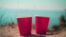 Dos tazas disponibles rojas de té en el fondo del mar y del horizonte metrajes