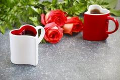 Dos tazas en forma de corazón con té y el ramo de rosas Imagen de archivo libre de regalías