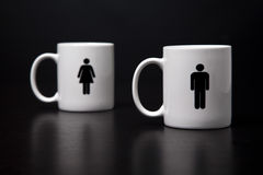 Dos tazas, hombre que se coloca delante de mujer. Fotos de archivo libres de regalías