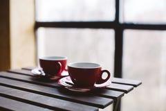 Dos tazas rojas en la tabla Imágenes de archivo libres de regalías