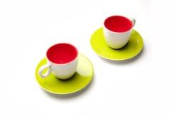 Dos tazas rojas y verdes en el aislante blanco del fondo Imagen de archivo libre de regalías