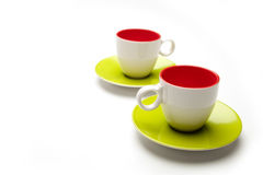 Dos tazas rojas y verdes en el aislante blanco del fondo Imagenes de archivo