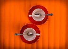 Dos tazas vacías blancas con té cucharean, en las placas rojas sobre fondo anaranjado del color, visión desde arriba Foto de archivo