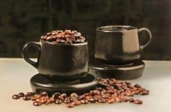 Dos tazas y granos de café Foto de archivo