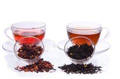 Dos tazas y platillos con negro y té de la fruta Imágenes de archivo libres de regalías