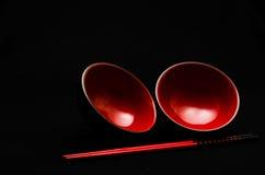 Dos tazones de fuente y palillos rojos en negro Fotografía de archivo libre de regalías